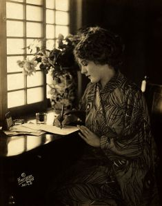 Mary Pickford writing with light from a Japanese-style window.