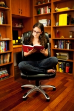 Young woman reading book at home library