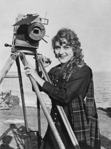 Mary Pickford, 1916, with movie camera. She's terribly cute with a scarf and curls in her long hair.