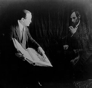 Black and White photo of magician Harry Houdini with ghostly image of Abraham Lincoln. They both seem to be looking at a book. Trick photography.
