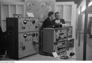 Large, clunky radio set in a studio, with two guys from the 1950s grimly discussing matters in the background.