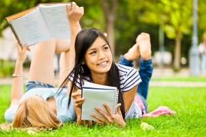 Girls laying on the grass with books