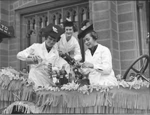 Black and white photo from 1937 showing three women in graduation caps and lab coats mixing up a science experiment while riding on a flower-bedecked car.