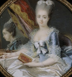 A duchesse sitting in front of a mirror holding a book.