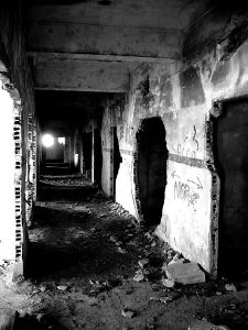 A hallway of a building that is being torn down. There is a circular light at the end of the dark hall.