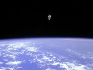 An astronaut in an untethered spacesuit floating above the Earth's clouds and oceans.