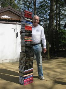 Roy F. Chandler standing next to a stack of the books he has written. Original photograph taken by Katherine R. Chandler 29 April 2009.