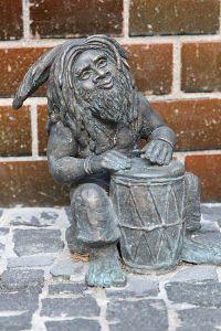 a dwarf drummer statue on cobblestones