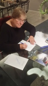 the author Lois McMaster Bujold signing at a glass table