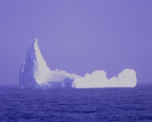 A blue-and-white picture of a big iceberg that looks like a castle.