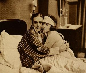 Black and white film still of a patient in bed (with a Japanese jacket) entwined with his nurse.