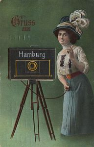 A young lady in the late 1800s with a giant black camera on a tripod