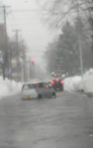 Cold and rainy winter day, street is banked with plowed snow, and the water is knee-deep. A small boxy car chugs through the water.
