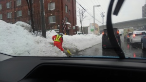 A road worker is digging out the snow bank that is blocking the storm drain. He's ankle-deep in water, and the puddle is starting to swirl around him.