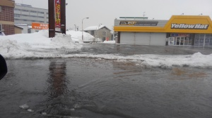 Water flooding the street and a parking lot, decorated with plenty of ice reefs.