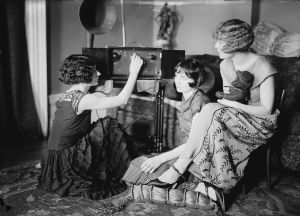 Three cute young women in the 1920s tuning their radio in the parlor. One is holding a teddy bear.