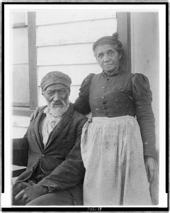 Elderly African American Couple from 1899 or 1900 on their front porch. She's strong and has her arm on his shoulder.