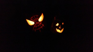Two jack o'lanterns at night (Spiderman, and a goofy one-toothed traditional pumpkin)