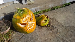 Two green jack o'lanterns. One is worse for the wear, and the other has collapsed inside itself in rot and despair.