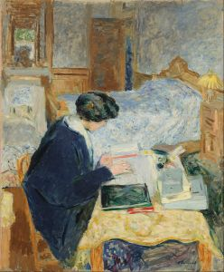 A lady reading at a desk in her bedroom. She's wearing a warm robe.