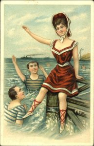 1908 girl in a skirted bathing costume having fun on a dock while two admiring boys splash in the water below.