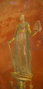 The muse Melpomene is standing on a tilted pedestal in this fresco. She holds a frowning mask in one hand, and a big stick resting on the ground with her other hand.