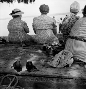 Older ladies sitting in the shade with their shoes off while others wade in the lake.