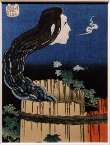 Okiku, a ghost from a well, at night. She's got a sad expression on her face, and she's blowing out a stream of cold air.