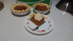 Two small pies in aluminum cases, with one slice on the plate, and enough whipped cream to fill a ping pong ball.