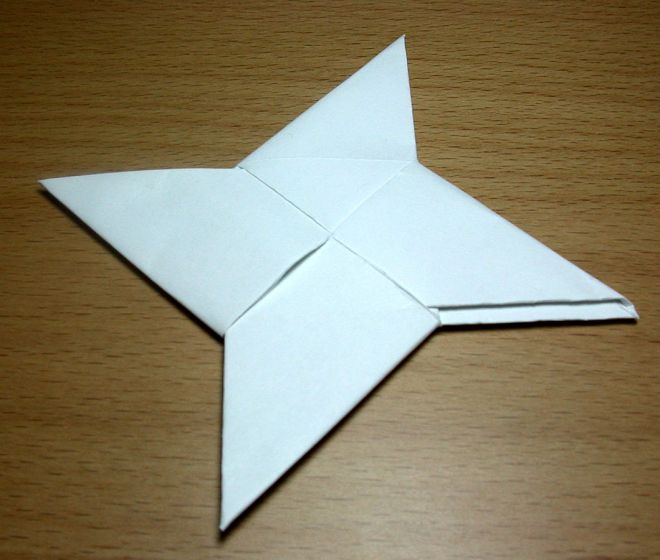 A shuri ken or Japanese Ninja star throwing knife in white paper. Four points