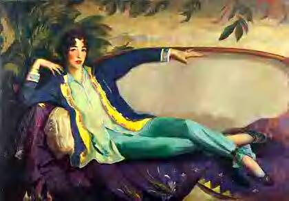 Woman lounging on a couch with a long jacket, long shirt and loose pants tied at the ankle