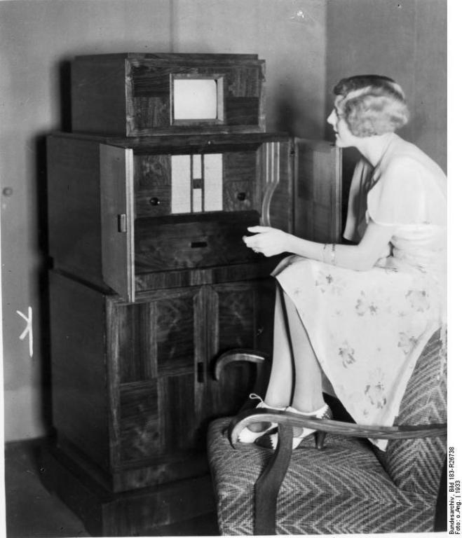 Young lady sitting on the back of a chair, watching a very small TV in a high cabinet c. 1933