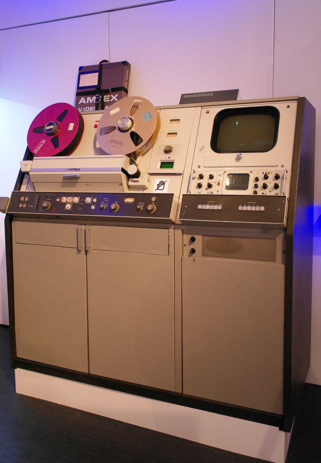 This is a picture of a Czech television recorder -- a small screen about the size of a laptop, huge reel-to-reel tapes, and on top of cupboards larger than those in a typical kitchen. This is a big piece of equipment, and it looks intimidating and a little grungy. Smoke from cigarettes, probably.