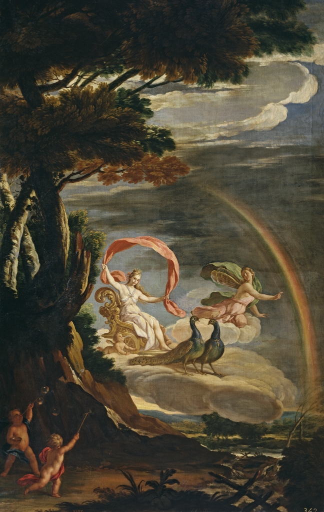 The pandemic bubble is represented by the arc of a rainbow. Inside are two goddesses and two peacocks. A tree completes the arc. Outside under the tree are two little cherubim, pointing at the goddesses.