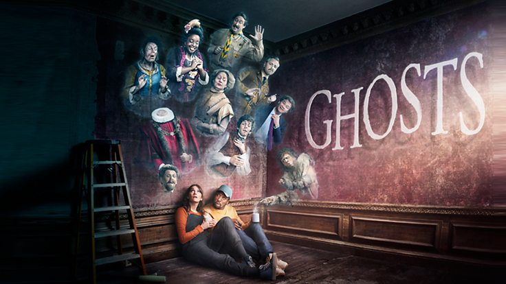 Alison (white woman) and Mike (Black man) sit on the floor during a DIY tea break, while ghosts come out the wall. GHOSTS is emblazoned on the wall.