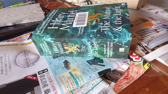 This paperback is 5 1/2 cm. thick. On top of a messy coffee table with Japanese magazines and advertisements.