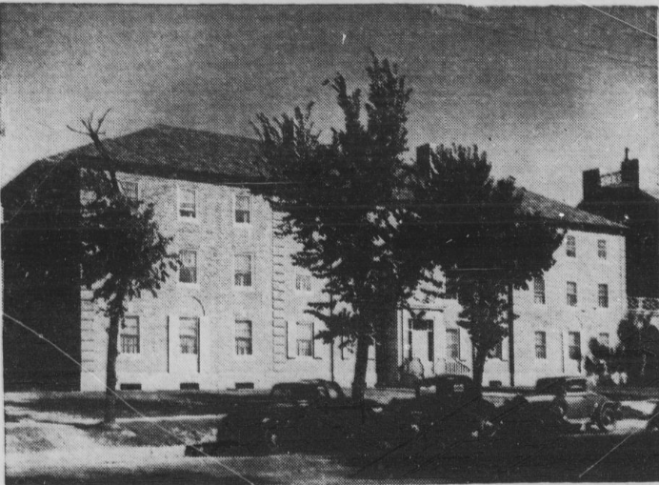 Black and white newspaper image of a three story dorm with basement.